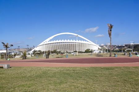 mabhida: DURBAN, SOUTH AFRICA - DECEMBER 4, 2014:  Viewing Moses Mabhida stadium from grass recreational area on Beach front  in Durban, South Africa