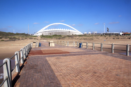 mabhida: DURBAN, SOUTH AFRICA - DECEMBER 4, 2014:  Viewing Moses Mabhida stadium from beach front pier in Durban, South Africa