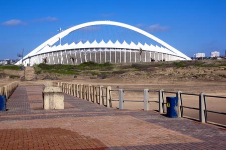 stadium  durban: DURBAN; SOUTH AFRICA - DECEMBER 4; 2014 : Moses Mabhida stadium viewed from pier on North beach in Durban South Africa