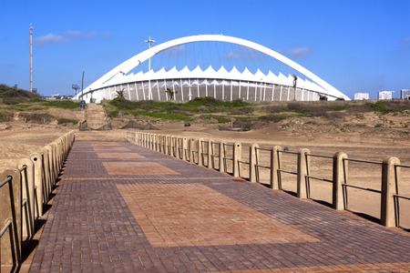 mabhida: DURBAN; SOUTH AFRICA - DECEMBER 4; 2014 : Moses Mabhida stadium viewed from pier on North beach in Durban South Africa