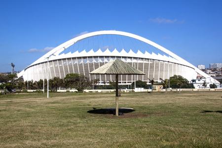 stadium  durban: DURBAN, SOUTH AFRICA - DECEMBER 4, 2014:  Viewing Moses Mabhida stadium from grass recreational area on Beach front  in Durban, South Africa