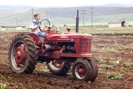 kwazulu natal: Richmond, KwaZulu Natal, South Africa - December 7, 2014: Unknown man demonstrating Vintage Farnall tractor at Natal Vintage Tractor and Machinary Club at Baynesfield Estate in Richmond, KwaZulu-Natal, South Africa