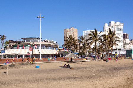 comercial: DURBAN, SOUTH AFRICA - DECEMBER 18, 2014: Many unknown people on early morning North Beach against comercial and residential Buildings in Durban, South Africa Editorial
