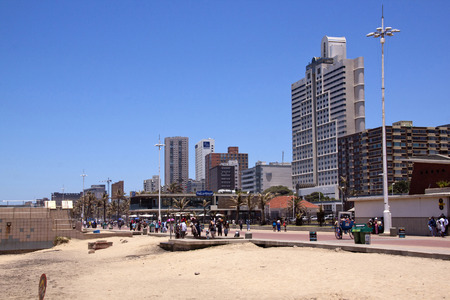 comercial: DURBAN, SOUTH AFRICA - DECEMBER 18, 2014: Many unknown people walk on promenade along North Beach against comercial and residential buildings in Durban, South Africa Editorial