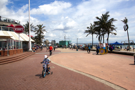 beach front: DURBAN, SOUTH AFRICA - DECEMBER 28, 2014: Many unknown adult and children cyclists and pedestrians on promenede on beach front in Durban, South Africa