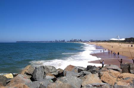stadium  durban: DURBAN, SOUTH AFRICA - DECEMBER 18, 2014: Many unknown fishermen fish on Blue Lagoon beach in Durban, South Africa