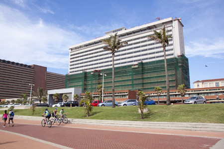 beachfront: DURBAN, SOUTH AFRICA - MARCH 15, 2015: Four pedestrians and cyclists on premenade in front of refurbished Addington Hospital on Glolden mile beachfront in Durban South Africa Editorial