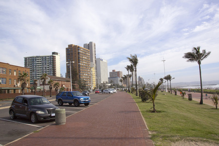 mile: DURBAN, SOUTH AFRICA - MARCH 15, 2015: Parked vehicles palm trees and Golden Mile city skyline in Durban, South Africa