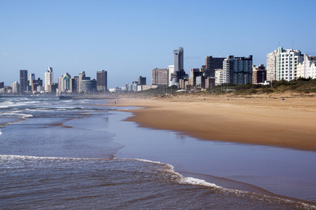 outgoing: DURBAN, SOUTH AFRICA - DECEMBER 4, 2014: Outgoing tide against city skyline on North Beach in Durban, South Africa