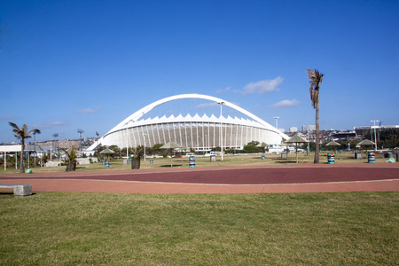 stadium  durban: DURBAN, SOUTH AFRICA - DECEMBER 12, 2014: Grass verge and promenade in front of Moses Mabhida Stadium in Durban, South Africa