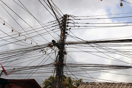 power cables: tangled web of cables connected to power supply on wooden pole