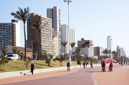 beach front: DURBAN, SOUTH AFRICA - JUNE 7, 2015: Many unknown people walk along promenade in front of commercial and residential buildings on Golden Mile beach front in Durban, South Africa Editorial