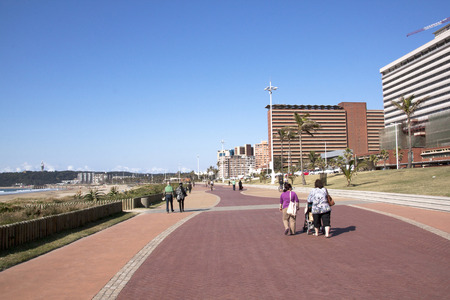 beach front: DURBAN, SOUTH AFRICA - JUNE 7, 2015: Many unknown people walk along paved promenade on beach front in Durban, South Africa Editorial