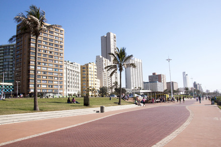 beach front: DURBAN, SOUTH AFRICA - JUNE 7, 2015: Many unknown people on beach front promenade against city skyline in Durban, South Africa