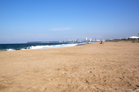 blue lagoon: DURBAN, SOUTH AFRICA - JUNE 12, 2015: Many unknown fishermen fish on Blue Lagoon beach against city skyline in Durban, South Africa