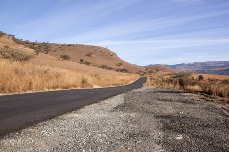 refurbished: Newly refurbished asphalt road leading through dry winter landscape in South Africa
