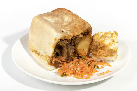 chow: Studio shot traditional durban bunny chow showing curry gravy soaked bread with carrot sambal Stock Photo