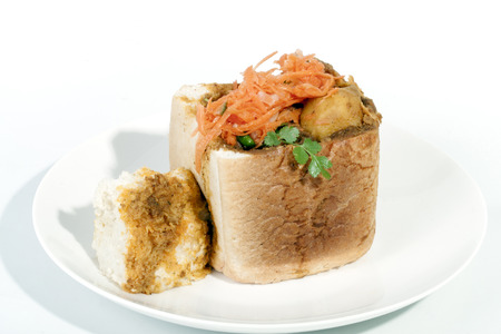 Studio shot traditional South African mutton bunny chow and carrot sambles Banco de Imagens