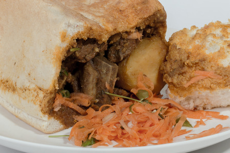 sambal: close up studio shot of traditional South African mutton bunny chow showing carrot sambal, meat and white bread