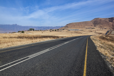 bordered: Straight empty asphalt country road road bordered with dry grass in South Africa Stock Photo
