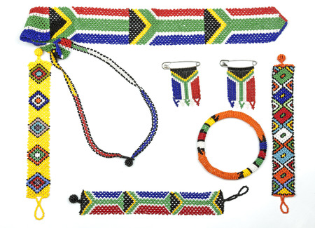 Above view of studio shot of variety of Zulu beadwork threaded into bracelets and flags on white Banco de Imagens
