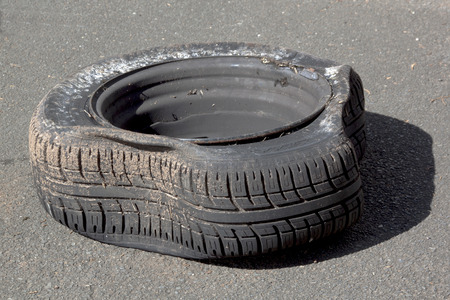deflated: dirty deflated damaged tire on metal rim after blowout on road Stock Photo