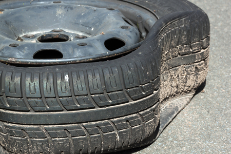 pot hole: closeup of dirty damaged deflated tire after blowout caused by pot hole in road Stock Photo