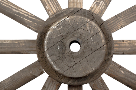 carreta madera: Side front closeup view of weathered hub and spokes of vintage handmade ornamental wooden wagon wheel on white Foto de archivo