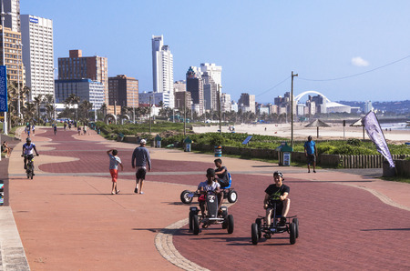 beachfront: DURBAN, SOUTH AFRICA - MARCH 23, 2016: Many unknown people walk and ride along paved promenade on Golden Mile beachfront against city skyline in Durban South Africa