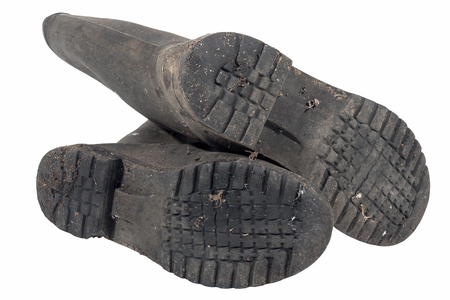 tread pattern: Under view of tread pattern on sole of dirty isolated pair of wellington boots