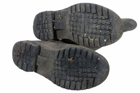 tread pattern: Isolated underview of tread pattern on soles on dirty pair of black  wellington boots