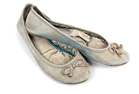 wornout: Pair of old well used blue tattered female worn-out shoes on white