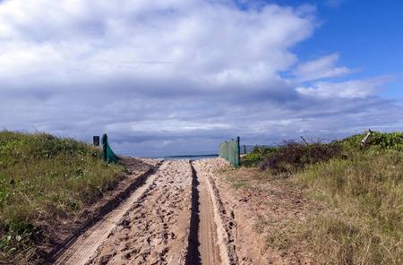 beach access: Beach access road lined with green shade cloth netting over sand dunes onto beach in Durban, South Africa Stock Photo