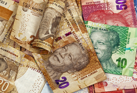rand: Closeup scattered collection of used South African twenty fifty and ten Rand brown red and green bank notes Stock Photo