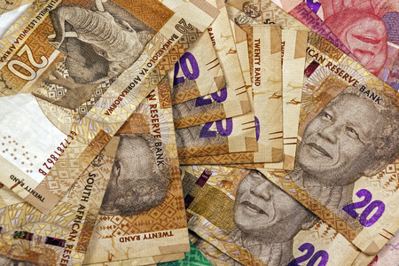 rand: Closeup scattered collection of used South African twenty and fifty Rand brown and red bank notes