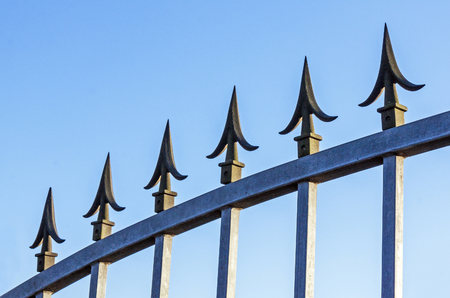 galvanised: Underview of spikes on galvanised gate against blue sy