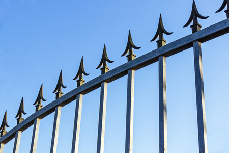 galvanised: Security pikes on galvanised gate against blue sy