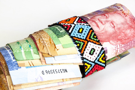 Roll of south african banknotes secured with band of Zulu beads