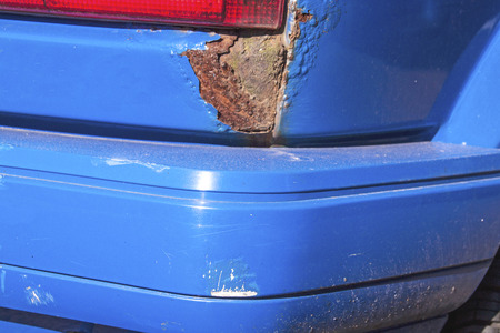 rust red: Closeup of severe rust and damaged bumper and red tail light on blue vehicle