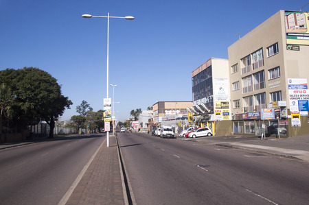 comercial: DURBAN, SOUTH AFRICA - JUNE 19, 2016: Empty early morning Umgeni road heading past comercial buildings and parked vehicles  towards city centre in Durban, South Africa