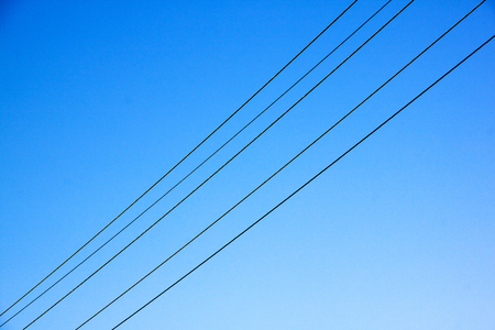 electricity supply: Five electric electricity supply cables stretching across blue sky Stock Photo