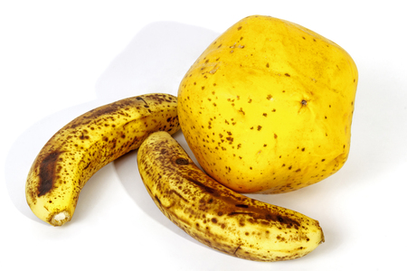bannana: Studio shot of two speckled ripe bananas alongside  yellow paw paw on white