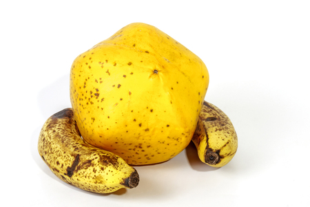 bannana: Studio shot of yellow paw paw hugged by two ripe speckled bananas on white Stock Photo