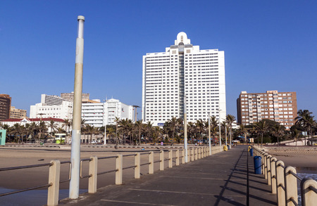 comercial: DURBAN, SOUTH AFRICA - JUNE 24, 2016: Early morning empty pier leads toward residential and comercial buildings on Golden Mile beach front in Durban, South Africa Editorial