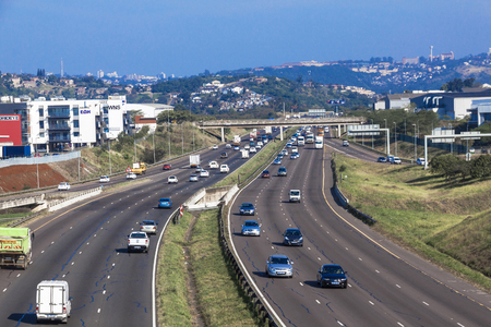 comercial: DURBAN, SOUTH AFRICA - JUNE 24, 2016: Many vehicles head north and south at mid day on the N2 highway at Riverhorse Valley comercial district in Durban, South Africa