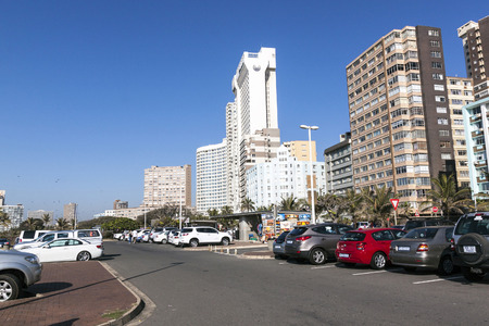 mile: DURBAN, SOUTH AFRICA - JUNE 26, 2016: Early morning many motor vehicles park on roadside in front of Golden Mile beach front city skyline in Durban, South Africa