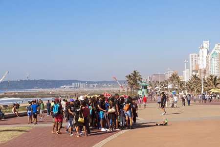 beach front: DURBAN, SOUTH AFRICA - JUNE 26, 2016: Many early morning unknown people gather on paved promenade on Golden Mile beach front against city skyline in Durban, South Africa