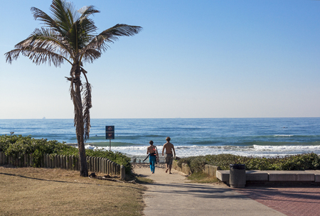 vegatation: DURBAN, SOUTH AFRICA - JUNE 26, 2016: Two unknown young boys walking onto beach past palm tree on beach in Durban, South Africa