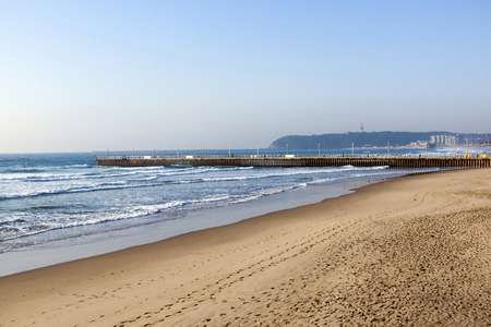 bluff: Early morning empty beach sea and concrete pier against blue sky and the Bluff in Durban South Africa