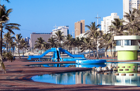 beach front: Blue swimming recreational pool area and palm trees against Golden Mile beach front city skyline in Durban South Africa Stock Photo
